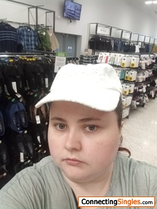 Trying new hats in the store to see which one suits me